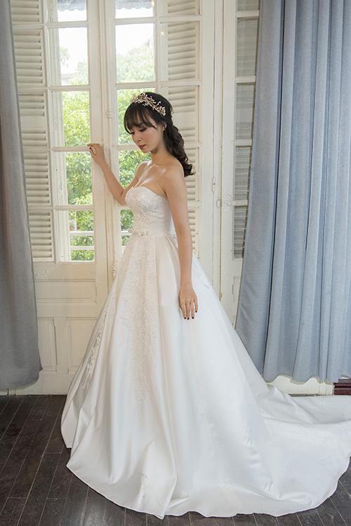 [Caption]Dáng váy bồng giúp tôn lên vẻ đẹp nhẹ nhàng, nữ tính của cô dâu phương Đông, nhưng vẫn thể hiện được sự gợi cảm qua đường cắt nửa kín nửa hở ở ngực. Kỹ thuật dựng 3D mới nhất được nhà thiết kế áp dụng trong bộ soiree bồng bềnh.