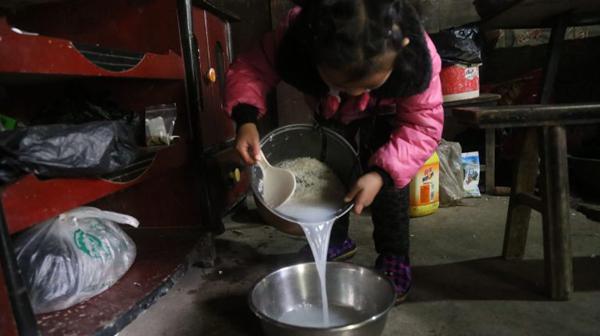 Anna vo gạo nấu cơm mỗi ngày.