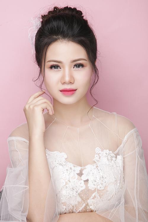 [Caption]Chuyên gia make up dùng cọ đánh môi đỏ hồng tươi trẻ, nổi bật, thu hút sự chú ý. Mái tóc búi trễ giúp cô dâu khoe trọn bờ vai đầy.