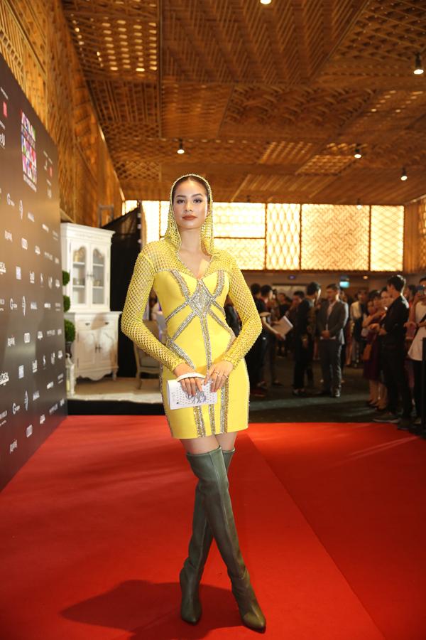 Phạm Hương chọn váy vàng nổi bật để phối với bốt cổ cao.