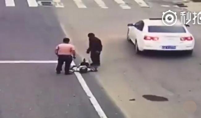 Cả tài xế xe tải lẫn người đi đường đều vội vã cứu giúp anh chàng lái môtô.