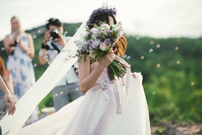 Váy cưới do chính Quỳnh Anh và cửa hàng váy cưới mà cô đang sở hữu lên ý tưởng và thực hiện. Chiếc váy được lấy cảm hứng từ loài hoa mà cô yêu thích nhất Hoa Lavender với sắc tím thanh nhã, ngọt ngào có điểm nhấn hoa thêu tinh tế màu xanh và tím pastel ở phần eo váy. Vì lễ cưới được tổ chức ngoài trời đòi hỏi sự linh động nên kiểu dáng váy cưới được thiết kế đơn giản, nhẹ nhàng nhằm tạo sự thoải mái nhất cho cô dâu.