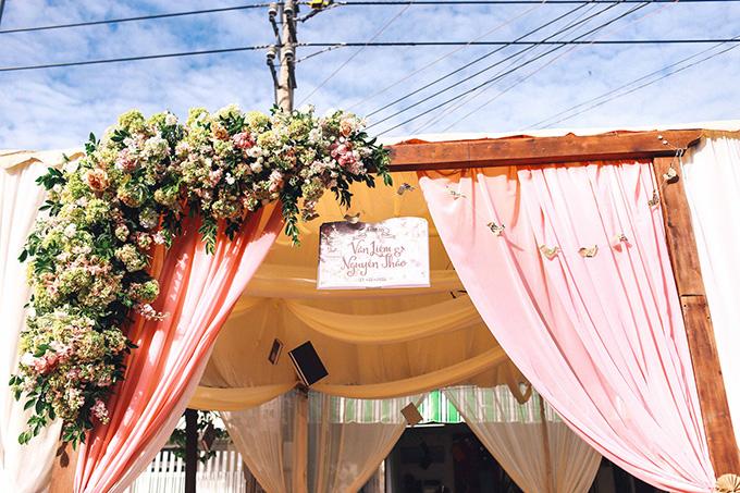 Phía cổng chào, một trang sách học trò màu hồng có in tên của cô dâu chú rể bên khóm hoa cùng tông, nổi bật giữa phố.