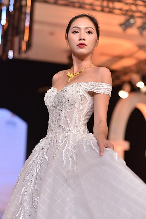 Váy cưới dáng cổ điển, chân váy xòe rộng được dựng phom bằng nhiều lớp vải lưới bồng bềnh với điểm nhấn là phần cúp chữ V ngang eo, trang trí họa tiết hoa thêu, bèo nhún... phù hợp với không gian tiệc cưới mang màu sắc cổ tích, lãng mạn.