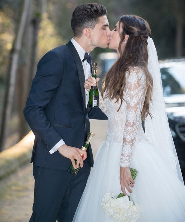 Trên tay cầm chai champagne mini, cô dâu chú rể đắm đuối hôn nhau.