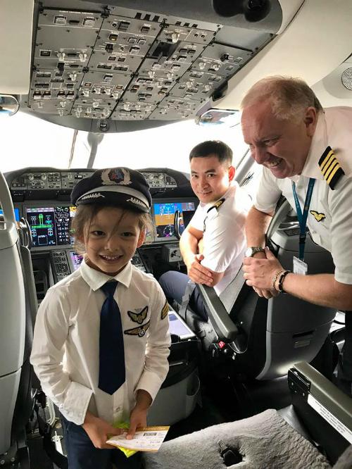 Bé Tôm nhà Hồng Nhung thích thú khi được mặc quần áo phi công đứng trong khoang lái máy bay trước giờ khởi hành.