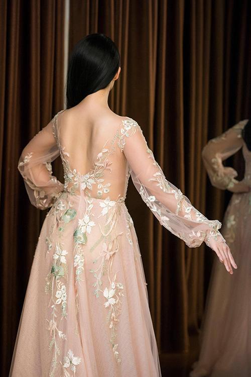 Nhà thiết kế sử dụng cách may phần ngực với voan trong suốt, tạo ảo giác trông như làn da của cô dâu, sau đó đính hoa ren điệu đà, nữ tính.
