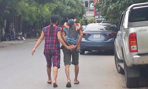 Chồng vừa cõng con vừa nắm tay vợ trên phố
