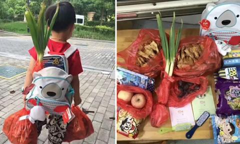 Cậu nhóc mang hành đi học để cầu may