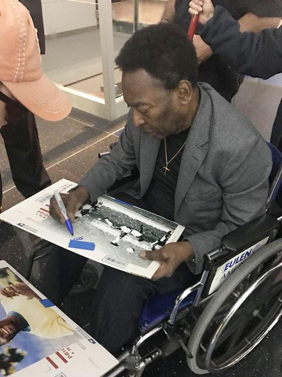 Vua bóng đá ngồi xe lăn lý tặng các fan tại sân bay.