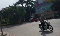 Cụ ông vừa đứng vừa điều khiển xe máy trên đường