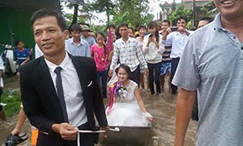 Rước dâu bằng thuyền trên đường phố ngày mưa lụt