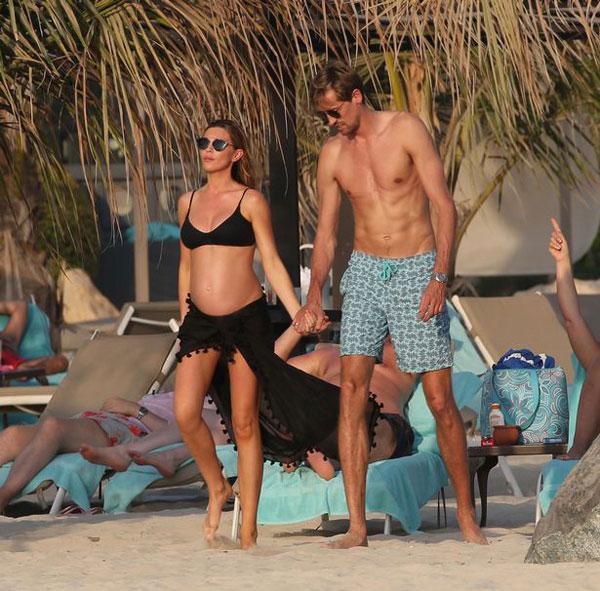 Vợ chồng chân sút người Anh nắm tay nhau đi dạo trên bãi biển thuộc khách sạn Royal Meridien