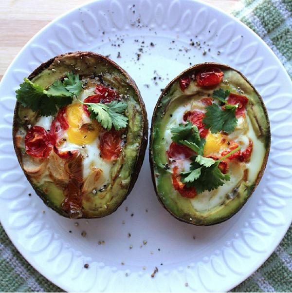 Món bơ ăn kèm trứng ốp đơn giản mà giàu protein. Bạn chỉ cần cắt đôi quả bơ, bỏ hạt, thêm trứng, các loại rau và một chút muối lên trên, nướng từ 20 - 22 phút rồi thưởng thức.