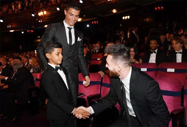 CR7 mỉm cười nhìn con trai bắt tay kình địch Messi. Ảnh: Sun