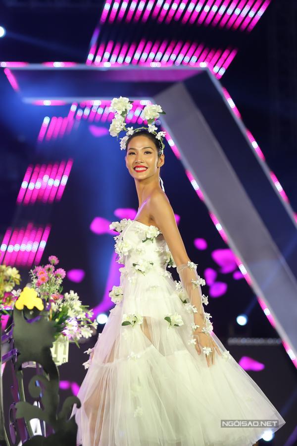 Hoàng  Thuỳ rạng rỡ trên sàn catwalk được thiết kế công phu với váy dạ hội được trang trí những cánh hoa tôn nét nữ tính.
