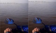 Sinh viên chạy xe máy trên sông đến trường