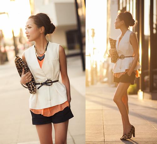 Cách mix layer độc đáo gồm áo sát nách màu cam và gile trắng.