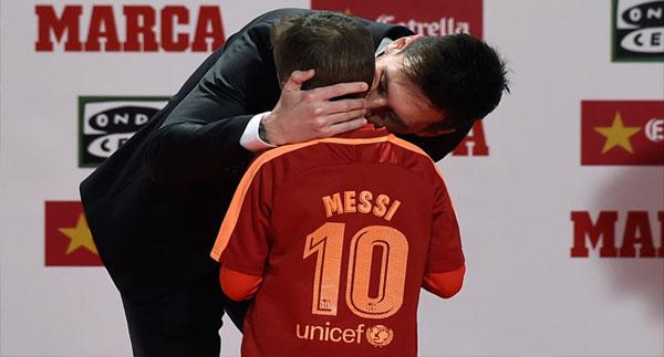 Messi ôm hôn một cậu bé khi lên bục trao giải.