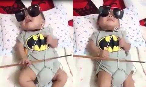 Bé trai ba tháng tuổi kéo đàn bằng đũa và mắc áo