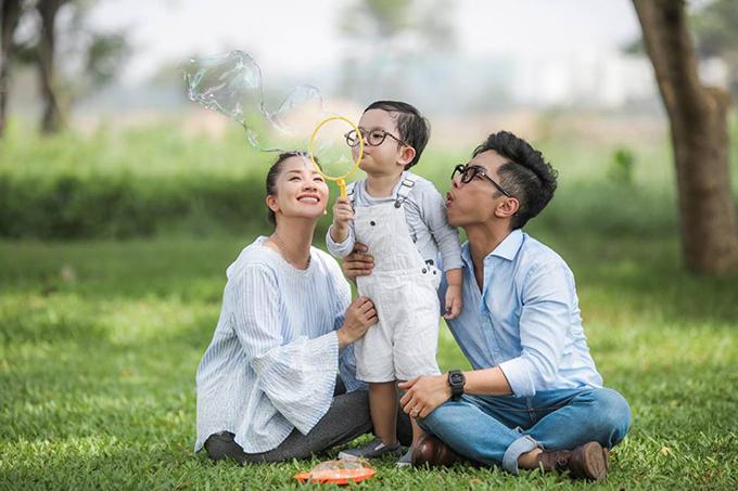 Kubi thích thú thổi bong bóng xà phòng trong buổi chụp hình với bố mẹ.