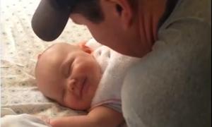 Bé sơ sinh đang ngủ nhoẻn miệng cười khi được bố hôn