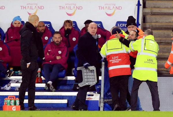 Fan cuồng chỉ tay, cố gắng nói điều gì đó với HLV Guardiola khi bị đưa ra ngoài.