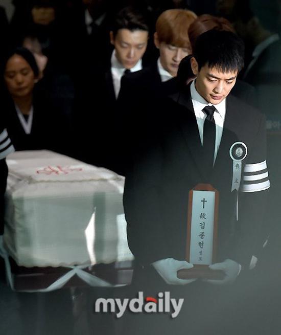 Minho ôm bài vị của Jonghyun, nỗi xót xa hiện rõ trên khuôn mặt anh.