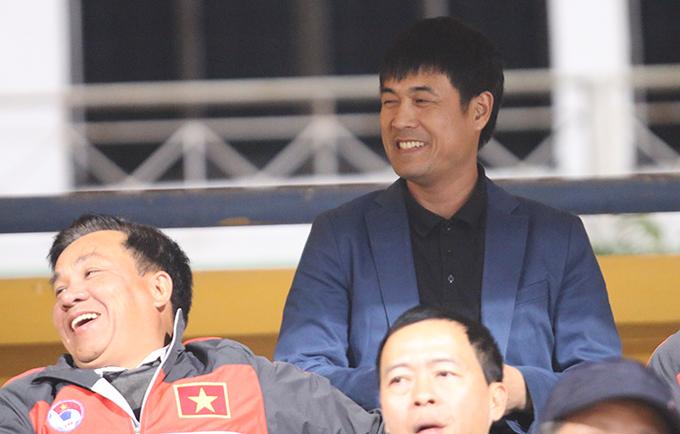 HLV Hữu Thắng nở nụ cười tươi khi trò chuyện cùng các đồng nghiệp trên khán đài.