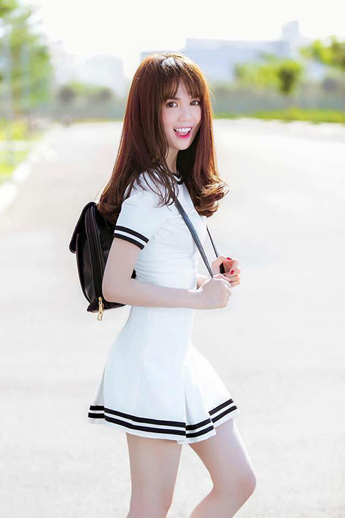 Ngọc Trinh hoá thành cô nàng nữ sinh, tóc mái ngố, mặc đồng phục trắng.