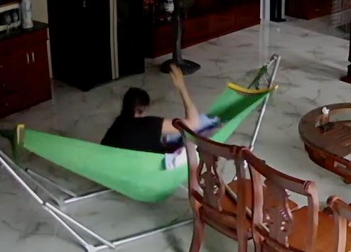 Bà Lý đánh em nhỏ khi đang nằm võng tại nhà. Ảnh chụp từ màn hình camera.