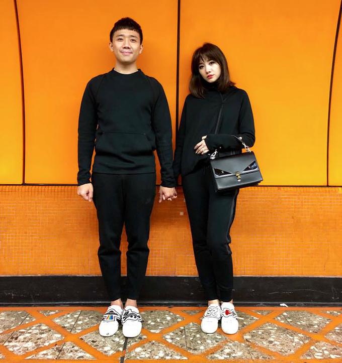 Trấn Thành nắm chặt tay Hariwon. Hai người mặc đồ đôi để kỷ niệm một năm ngày cưới.