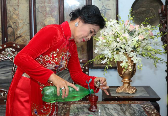 Mẹ nữ ca sĩ châm thêm dầu để chuẩn bị cho nghi thức lên đèn trong ngày vu quy của con gái.