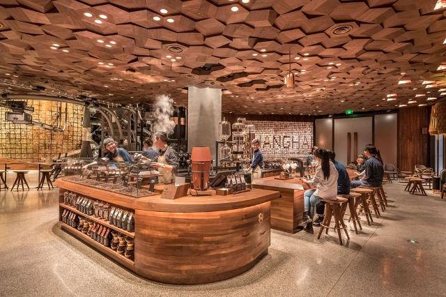 Concept của cửa tiệm mới này hướng tới sự đơn giản, mộc mạc với đồ nội thất 100% làm từ gỗ như bàn ghế, kệ đồ dùng, trần nhà cũng được ốp gỗ theo kiểu tổ ong. Cửa hàng được đặt tại một căn nhà có phần mặt tiền cong qua 2 mặt phố, không gian bên trong rất rộng rãi.