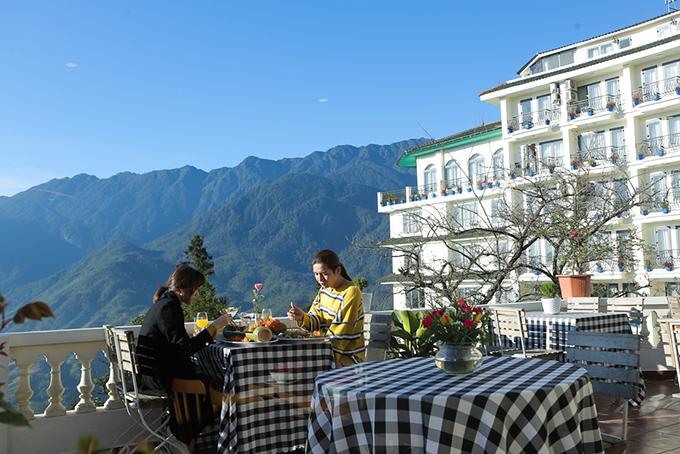 Cặp đôi dùng bữa sáng giữa không gian trong lành của khu resort.