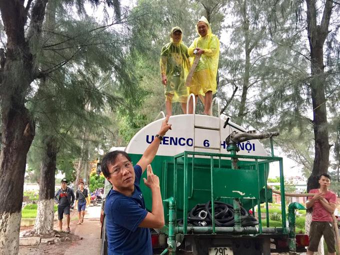 Đạo diễn Trọng Trinh tạo dáng hài hước bên xe chở nước làm mưa nhân tạo cho một cảnh quay.