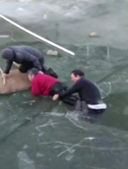 Lei được một người đàn ông khác hỗ trợ đưa cụ bà lên bờ. Ảnh: Reuters