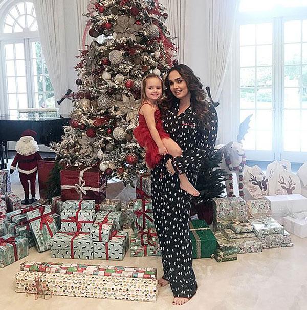 Hai mẹ con người đẹp Tamara đứng cạnh cây thông Noel cao lớn cùng núi quà.