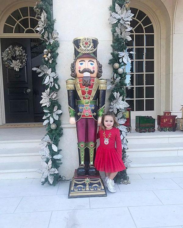 Con gái Tamara mặc váy hồng đáng yêu, đứng tạo dáng cạnh bức tượng.