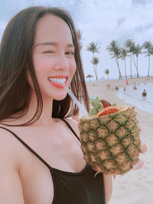 Người đẹp Vũ Ngọc Anh sang Singapore, cô thảnh thơi uống nước dứa trên bờ biển Tanjong.