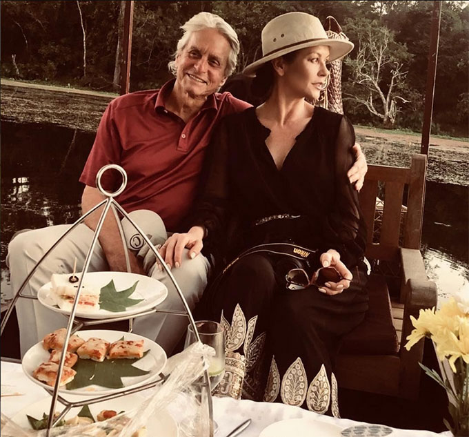 Không chỉ đến Ấn Độ, gia đình Douglas còn tới thăm Campuchia. Vợ chồng nam diễn viên tình cảm bên nhau tại một quán ăn ven sông.