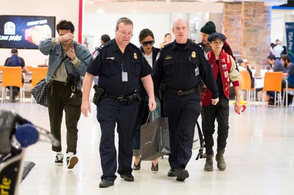 Hai vệ sĩ cao to xách đồ và bảo vệ gia đình cựu danh thủ Anh tại sân bay ở Los Angeles.