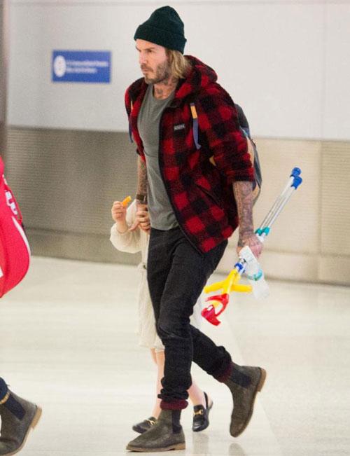 Becks với gương mặt kém vui, cau có tại sân bay. Cựu sao 42 tuổi cầm theo một đôi nạng trẻ em, có vẻ Harper đang bị đau chân.