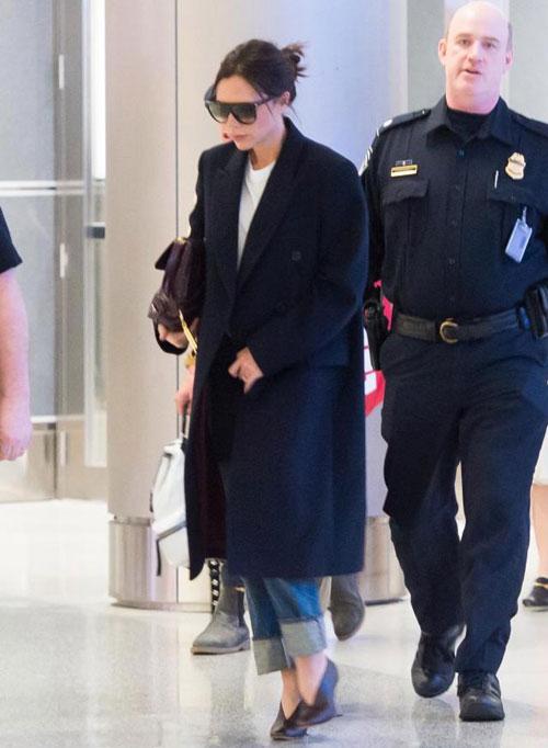Vic ôm túi xách nhỏ, thảnh thơi bước đi ở sân bay.