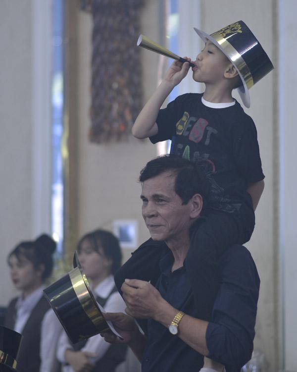 Bố ruột Hà Hồ công kênh cháu ngoại trên vai để bé nhìn cho rõ mẹ trên sân khấu.