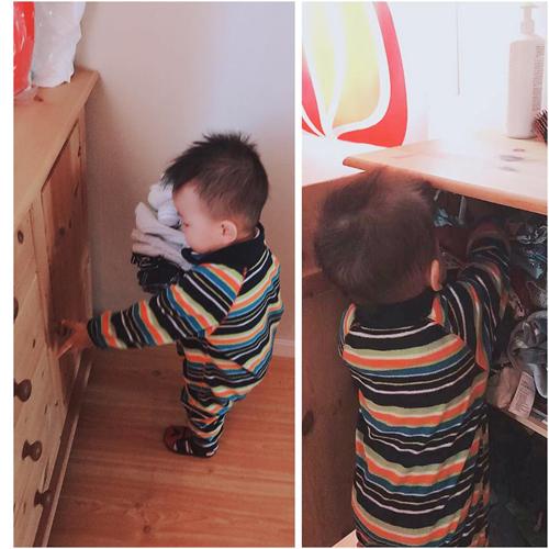 Bé Rio giúp mẹ xếp quần áo vào tủ.