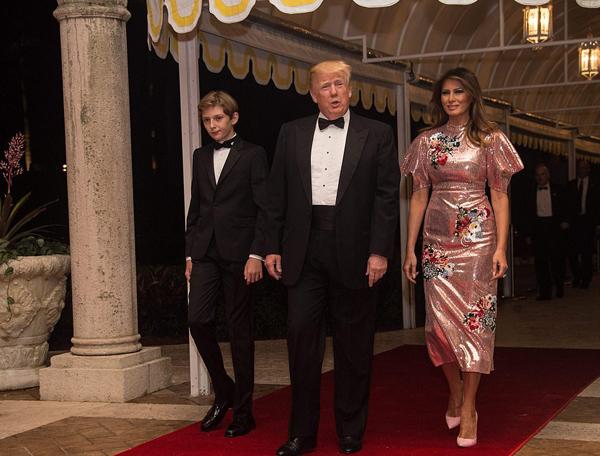 Sánh vai chồng đến dự tiệc, bà Melania thu hút ánh nhìn khi diện chiếc váy sequin hồng thêu hoa lấp lánh của Erdem, trong khi ông Trump và quý tử 11 tuổi mặc vest đen lịch lãm, thắt nơ ở cổ.