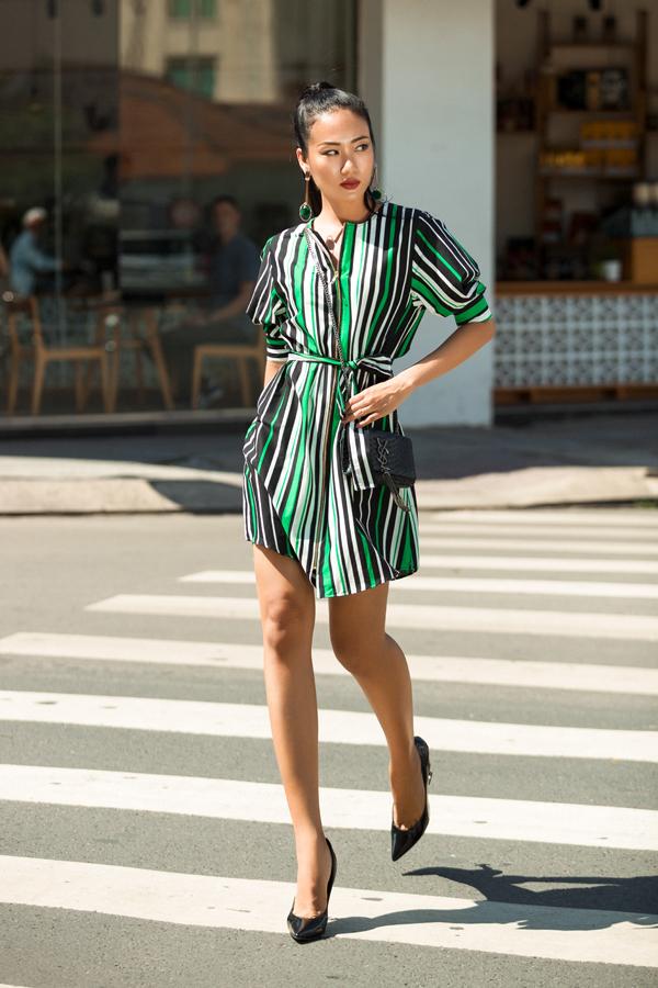 Phối cùng mẫu trang phục có họa tiết dễ dàng giúp bạn gái ăn gian chiều cao là các phụ kiện giày cao gót, túi đeo chéo phom midi đồng sắc đen.