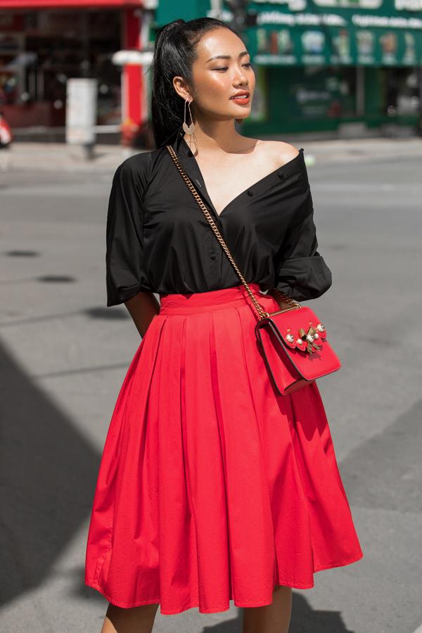 Cách phối màu đỏ đen được áo dụng một cách hiệu quả với sơ mi dáng rộng đi cùng chân váy midi theo phong cách cổ điển. Hoa tai ghim băng, túi đeo chéo trang trí hoa nổi là các món phụ kiện được chọn lựa để hoàn thiện set đồ dạo phố.