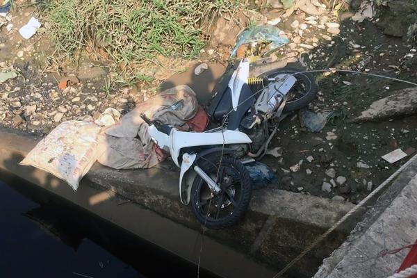Xe máy ngã, nằm sát mép nước. Ảnh: Tin Tin